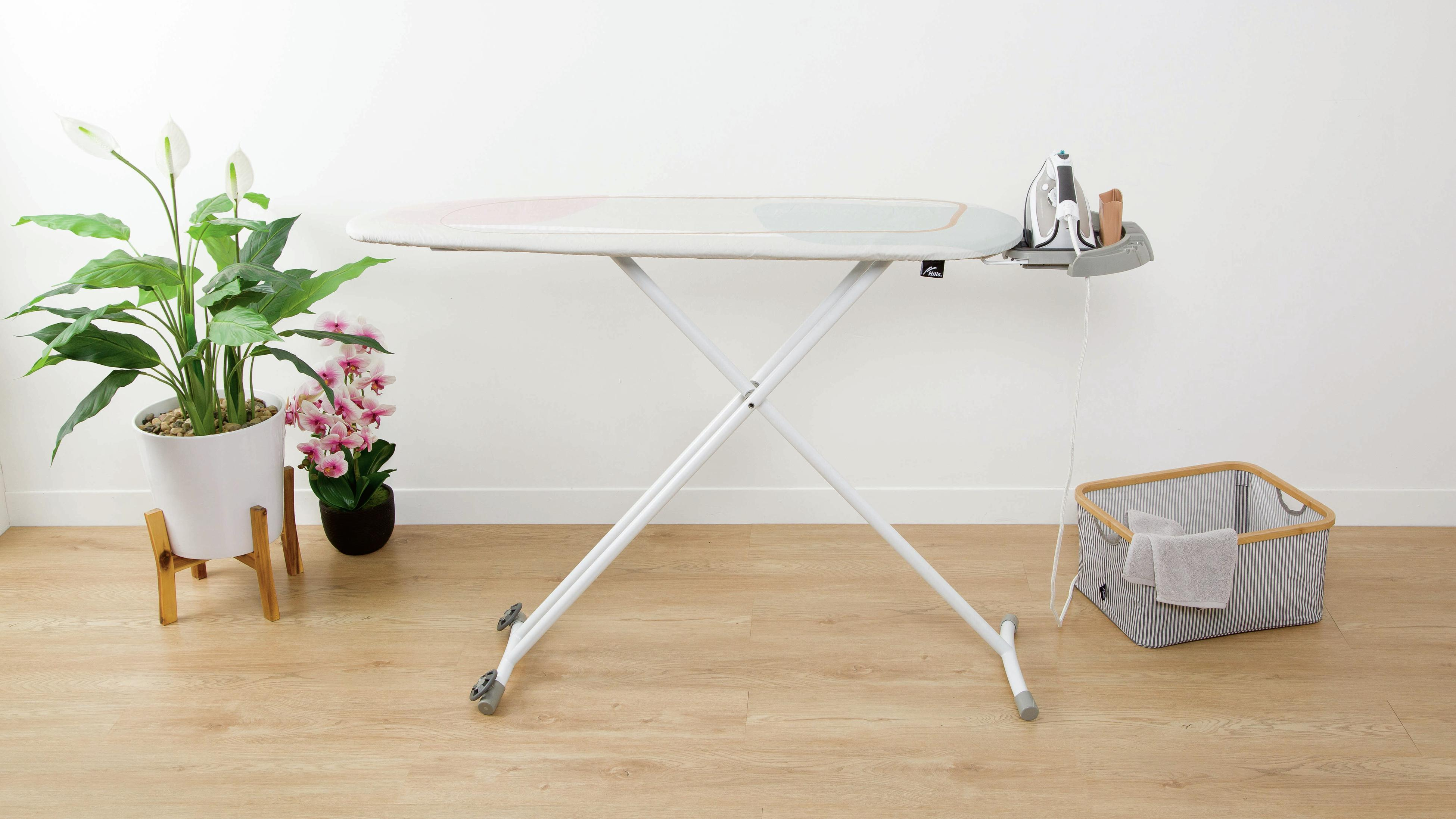 Ironing board, iron and clothes basket in a living room