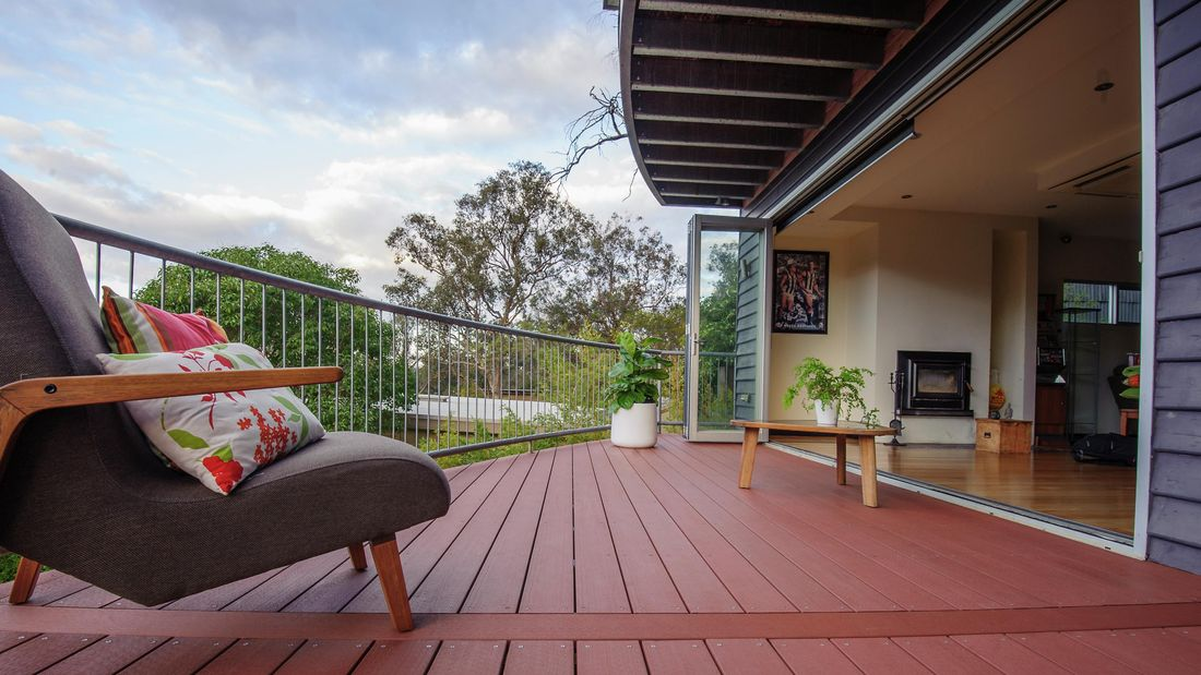 A deck leading out from a living space separated by bay windows