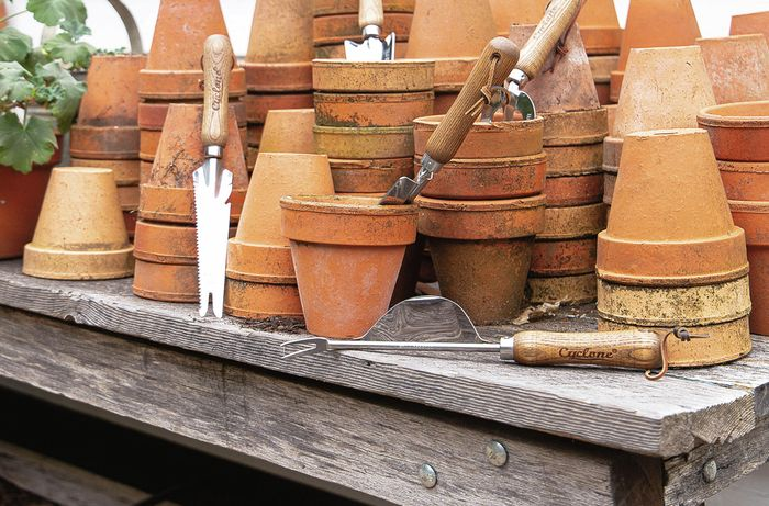 Garden hand tools placed in terracotta plant pots
