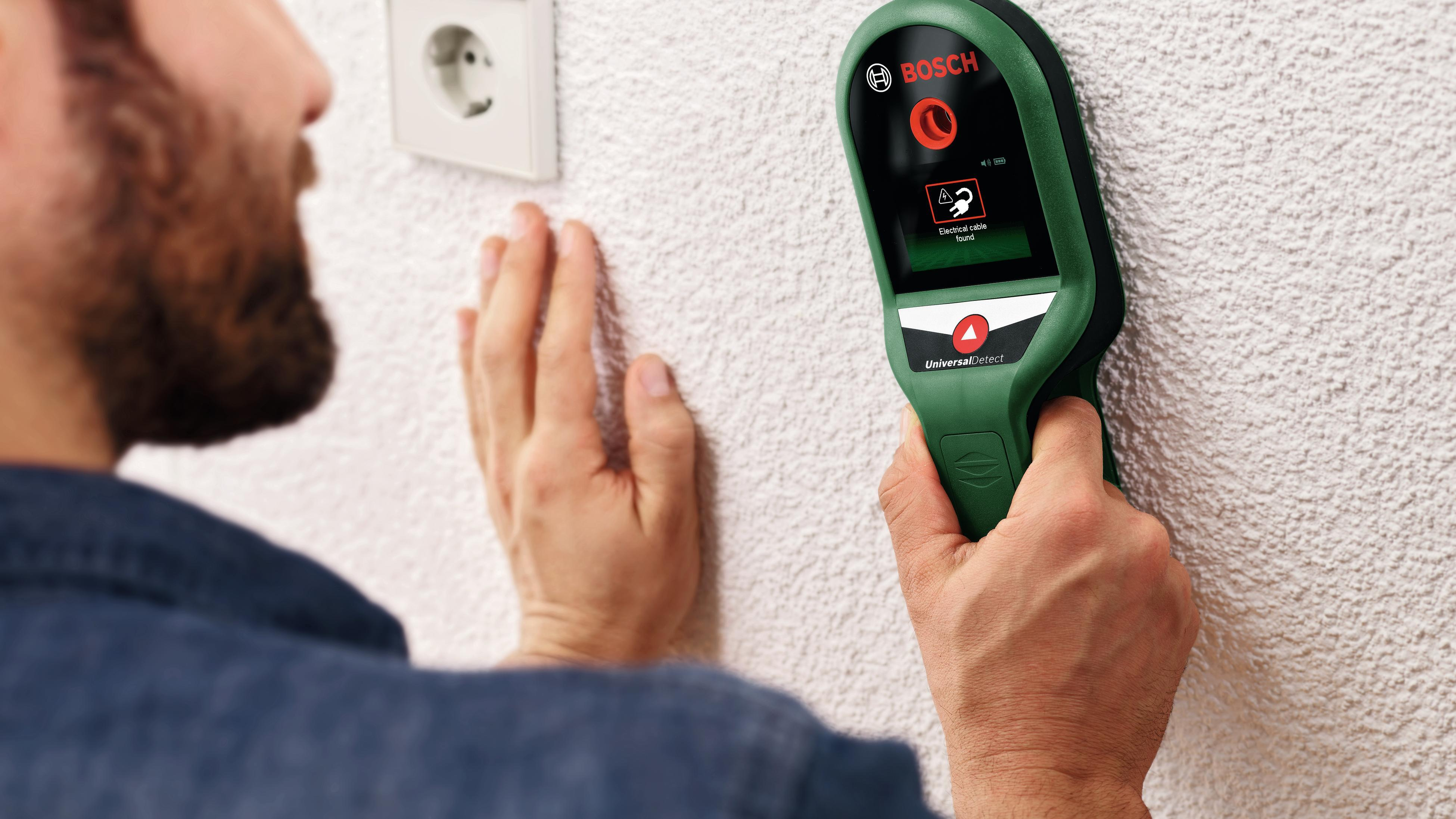 Person using stud finder on wall.