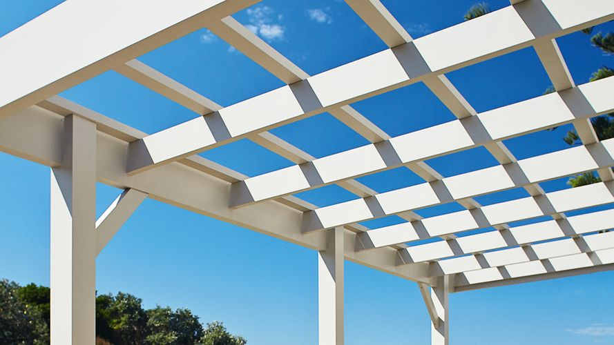 View of a white painted pergola looking upwards to blue sky