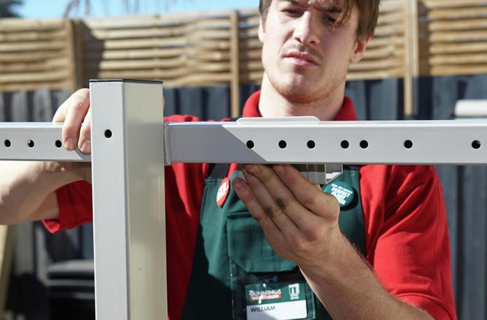 A Bunnings team member attaching the hooks to the universal bracket.