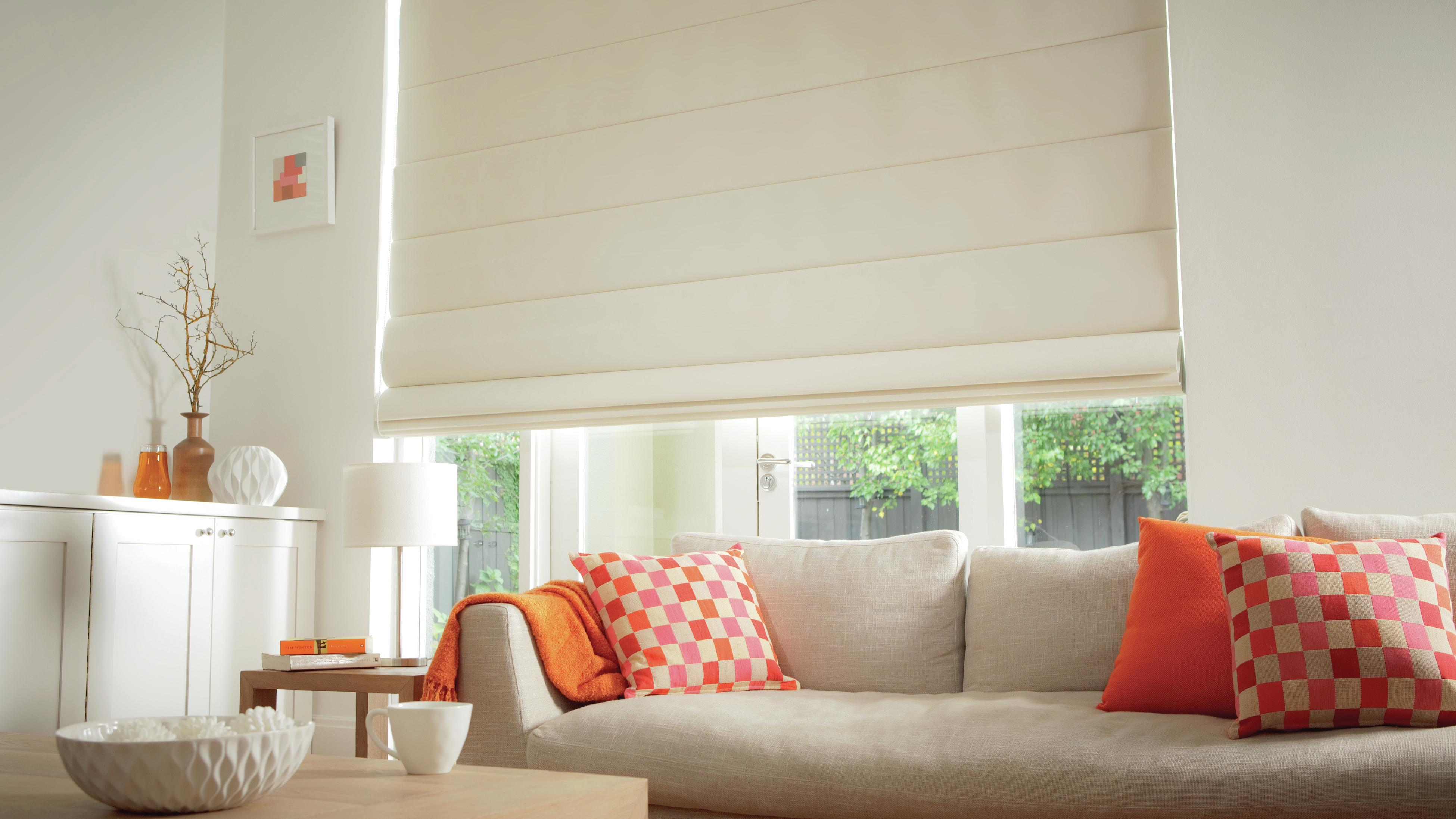 A living area with a cream couch, orange cushions and white Roman blinds.