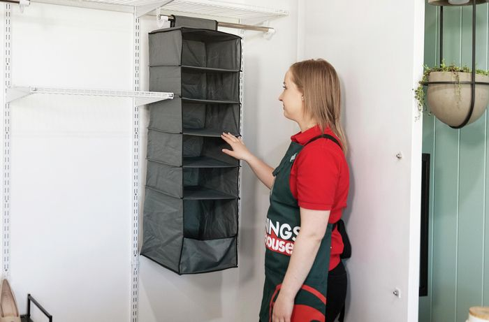 A person looking at a hanging shoe rack inside a wardrobe