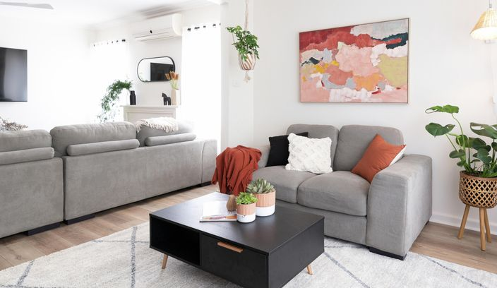 Living room with grey couches, coffee table and rug.