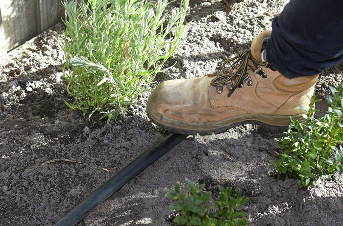A person pushing down a pin with their boot to secure poly pipe