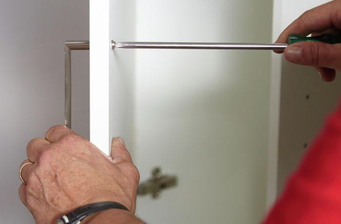 Person screwing handle to panel door.