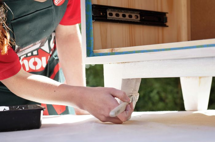 Person painting the legs of a wooden bedside table