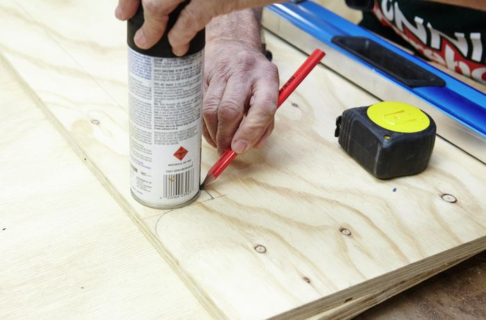 Person tracing can on ply panel to mark circular cuts