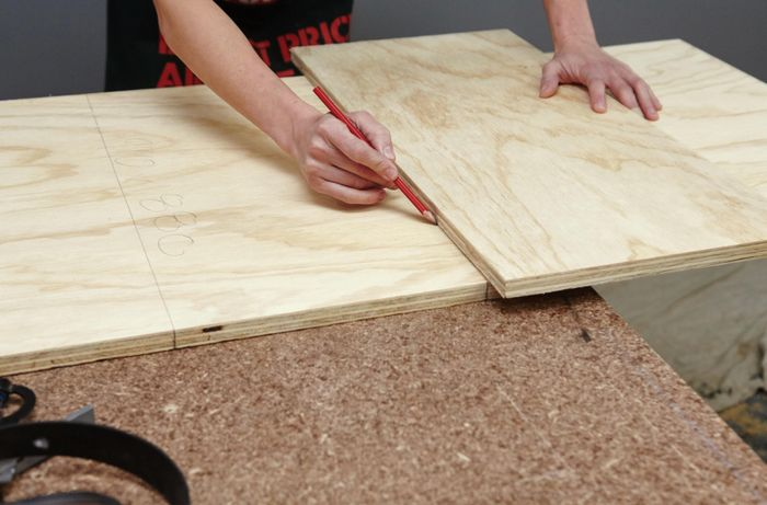 A person drawing a line on a plywood sheet using another sheet as a straight edge