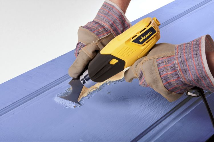 Person using a heat gun to remove paint from timber