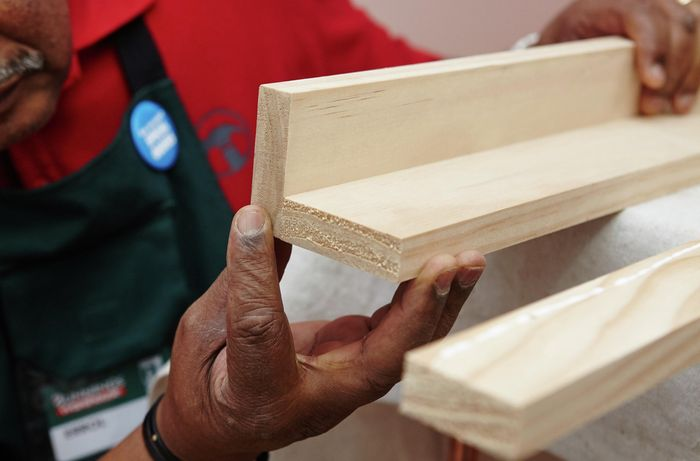 A person holding two lengths of pine timber joined to make an L shape
