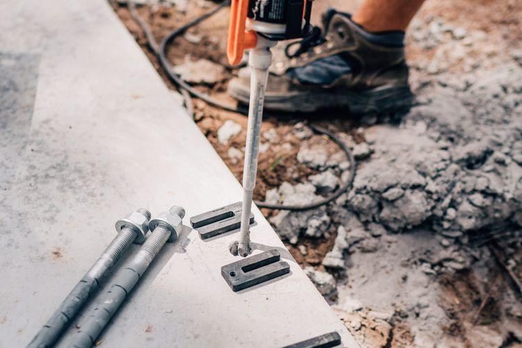 Person adding epoxy to hole in concrete