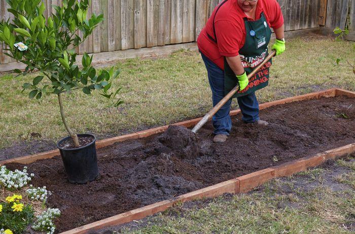 A Bunnings team member shovelling potting mix into a garden bed