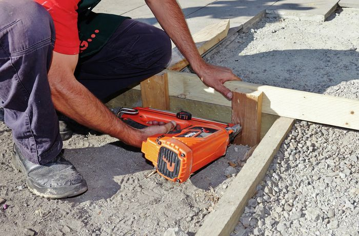 Person using nail gun on piece of timber.