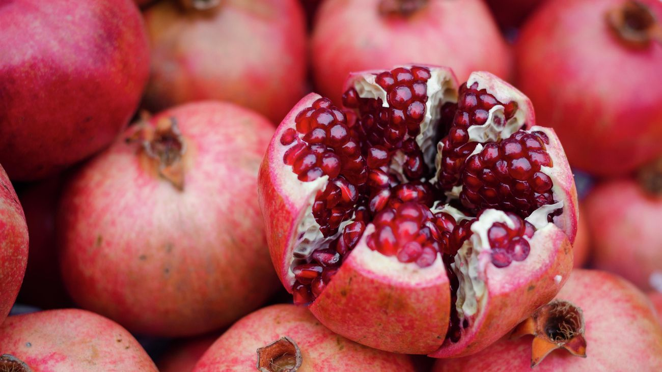Red pomegranate fruits, one cut open to reveal seeds