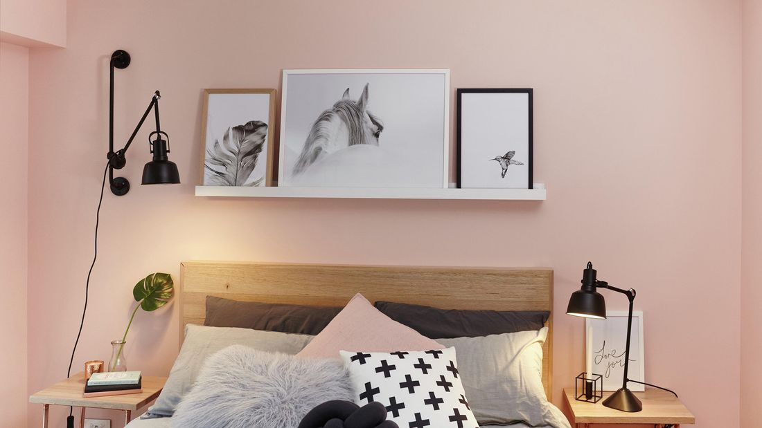 A floating white shelf with framed pictures above a bedhead against a pink wall