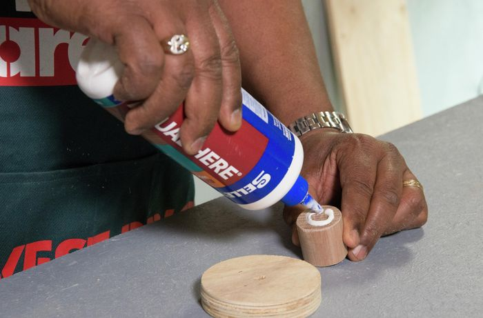 A person applying glue to the end of a dowel rod