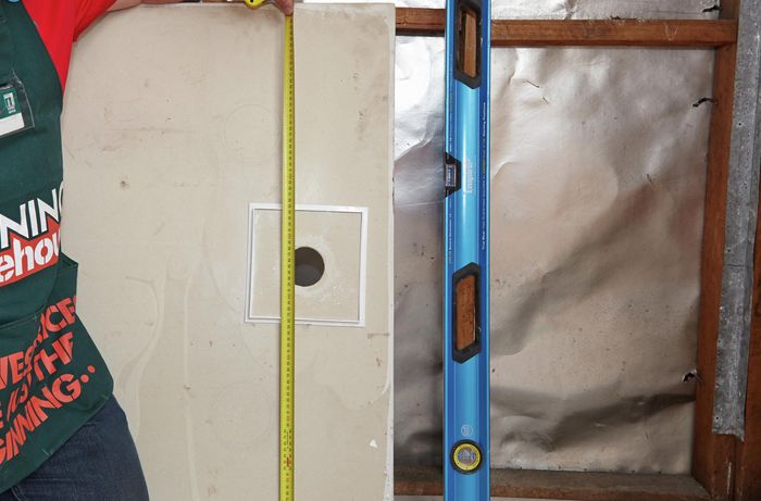Measuring the width and length of a shower sump along a floor sheet, along with a spirit level used to align the sump