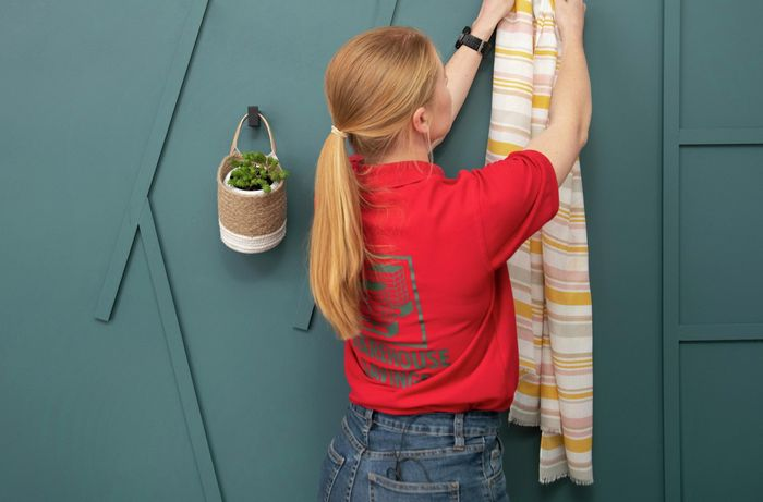 Person hanging towel on wall using a hook.