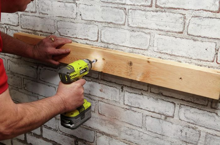 Person drilling timber into wall.