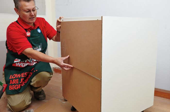 Person attaching back to cupboard