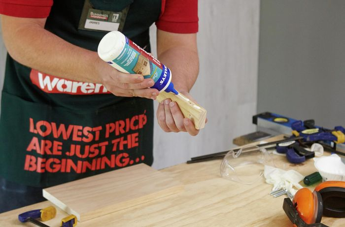 A person applying glue to a small piece of wood