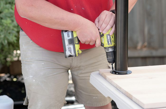 A Bunnings team member securing a table leg to a piece of timber