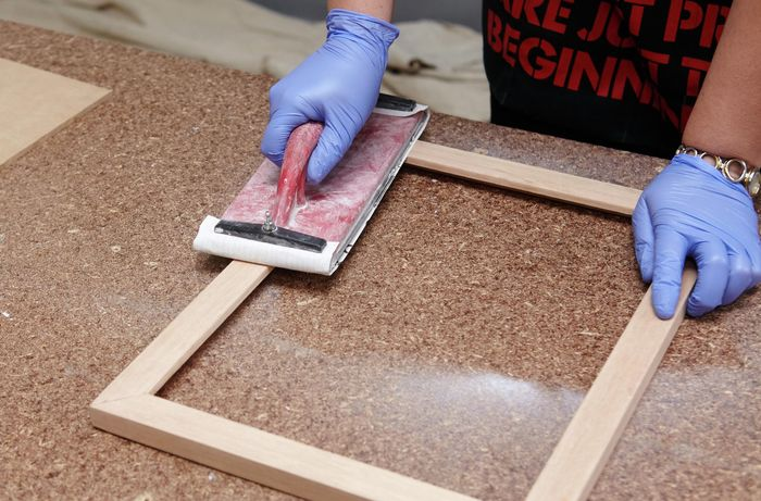 An assembled picture frame being sanded down with a hand sander