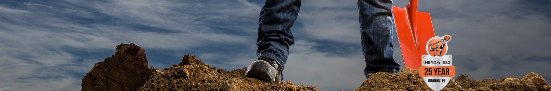 Tradie standing on pile of dirt.