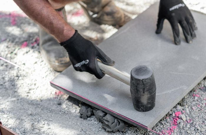 Person wearing work gloves tapping a paving stone placed on top of mortar with a rubber mallet.