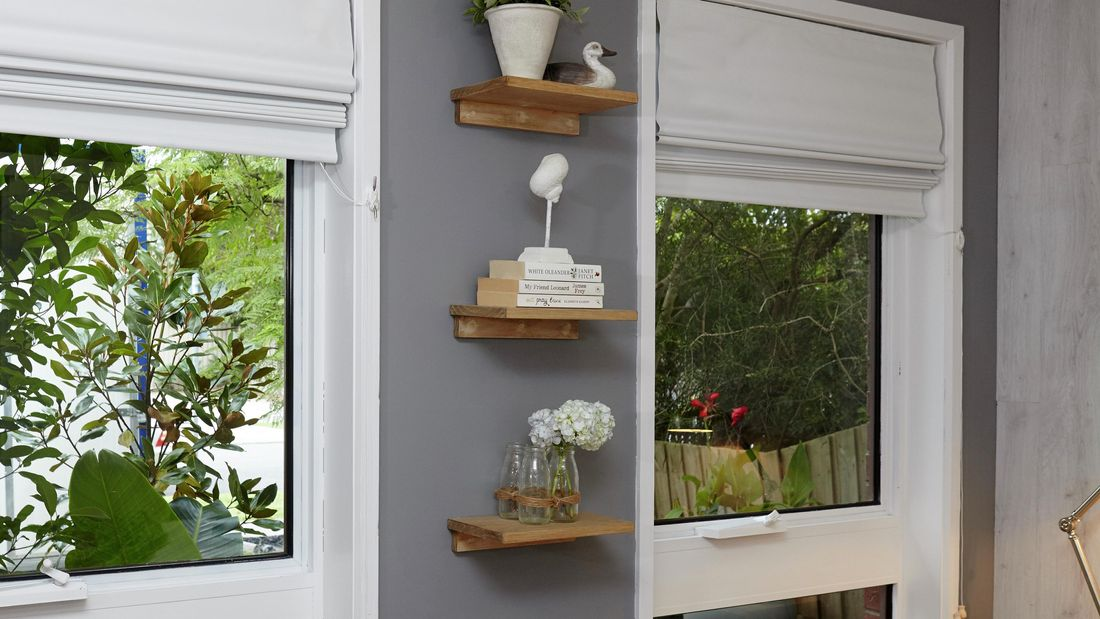 Three small timber shelves arranged vertically between two windows