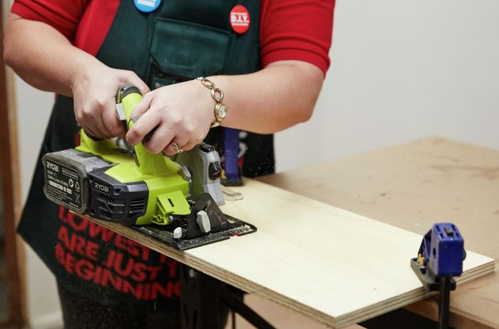 A person cutting a sheet of plywood using a circular saw