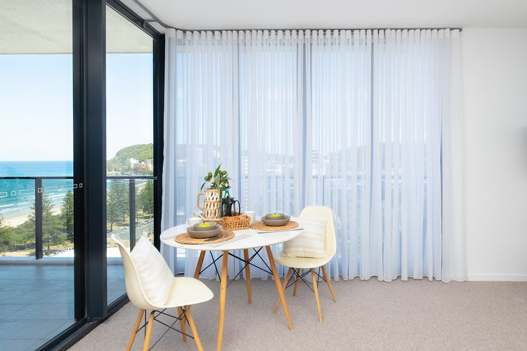 Seaside apartment with sheer curtains covering windows