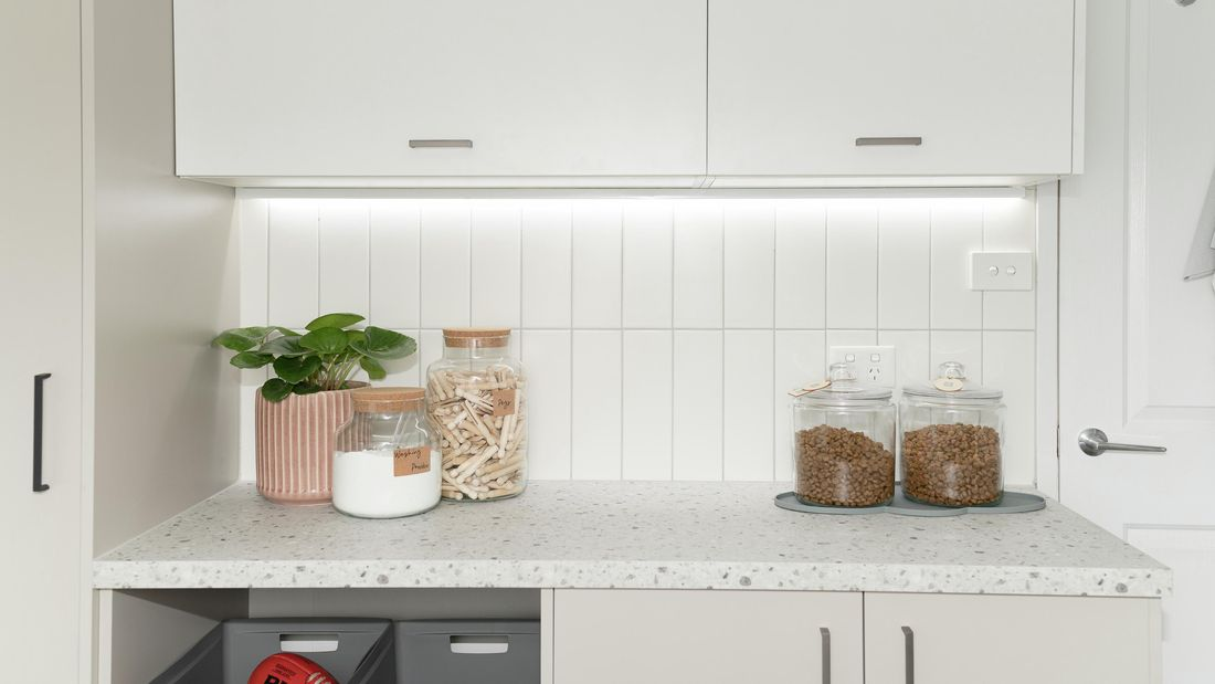 Laundry with cabinets, basket pull outs and decorative items.