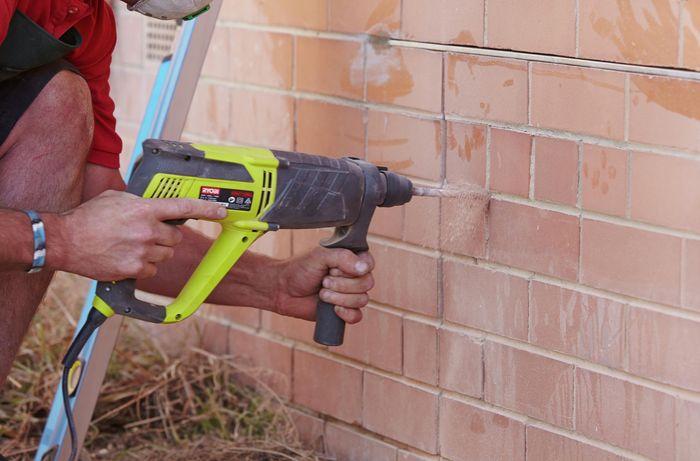 A hammer drill being used to loosen mortar between bricks