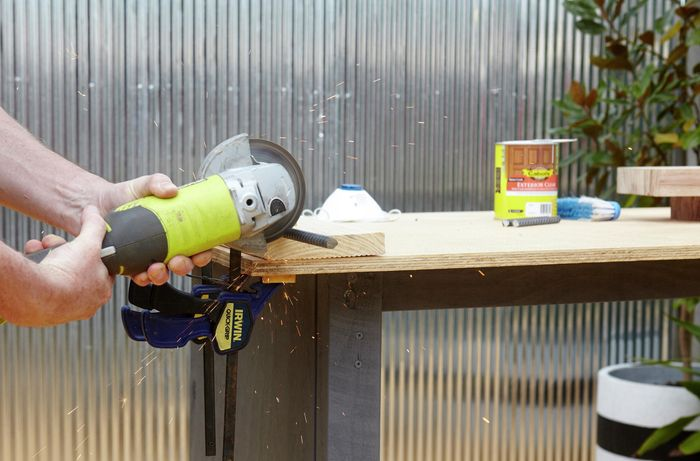 Person cutting bit of timber with handheld saw.