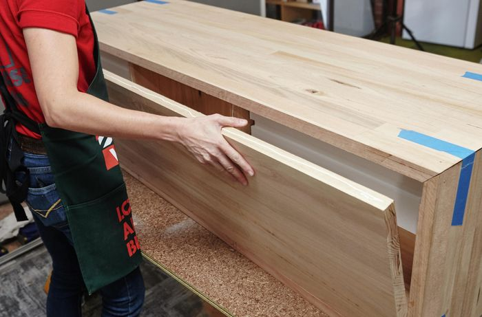 A person fitting a back panel into the sides and top of a timber vanity unit