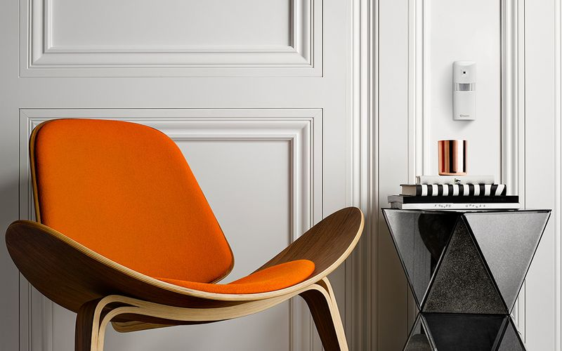 Stylish orange chair against a white painted wall with a mounted movement sensor