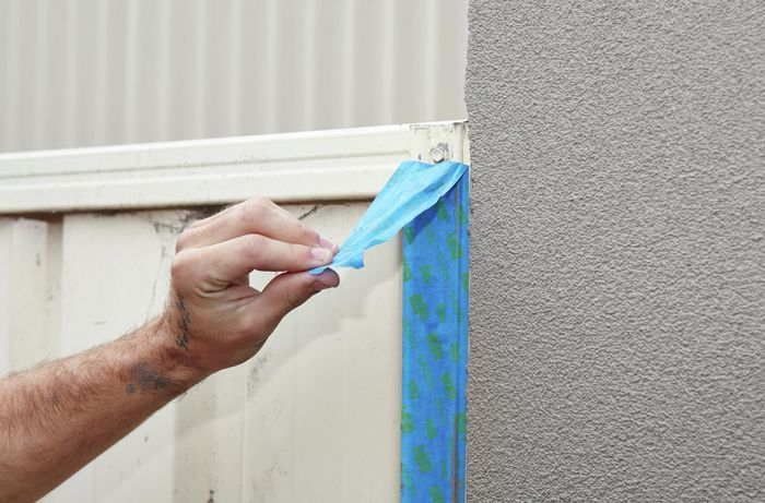 Painters tape being peeled free of a wall corner