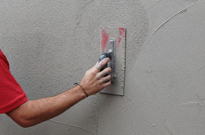 A trowel being used to smooth render on a wall