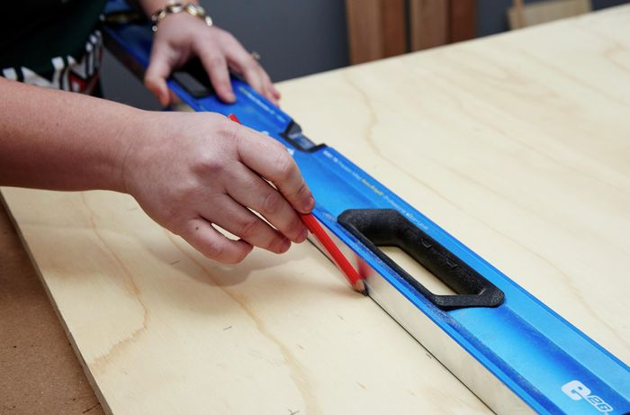 A person drawing a line on a plywood sheet using a spirit level