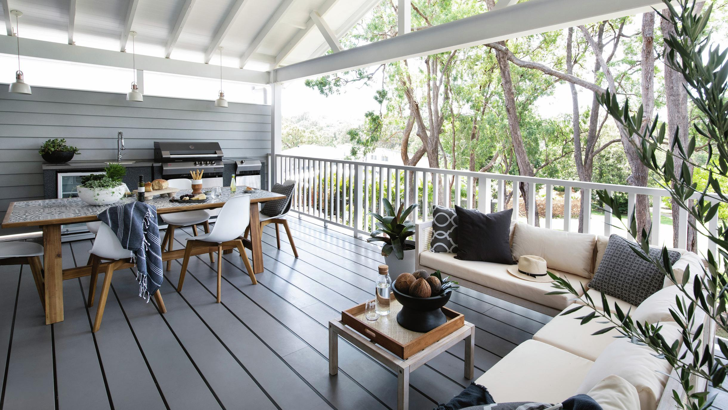 Outdoor area featuring dining and lounge furniture, and BBQ, on top of grey deck.