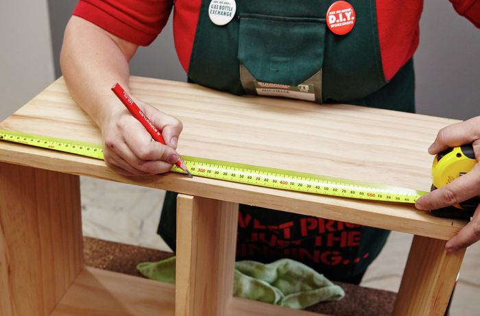 A tape measure and pencil being used to mark a kids wooden storage bench for screw holes