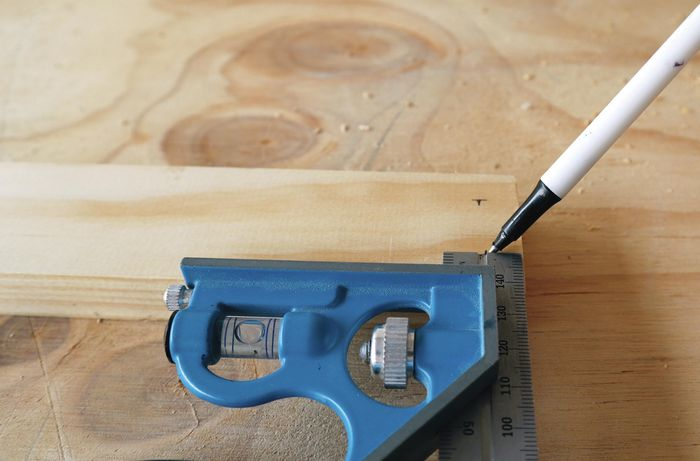 Person measuring and marking hole locations for drilling