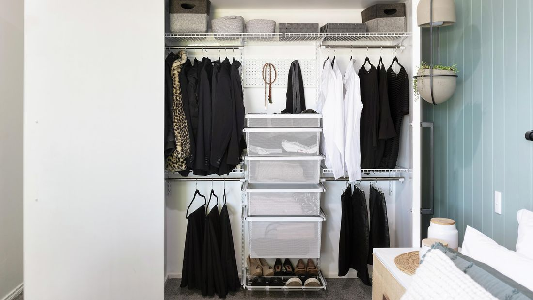 An empty wardrobe with hangers, wire mesh drawers, a pegboard and overhead wire rack