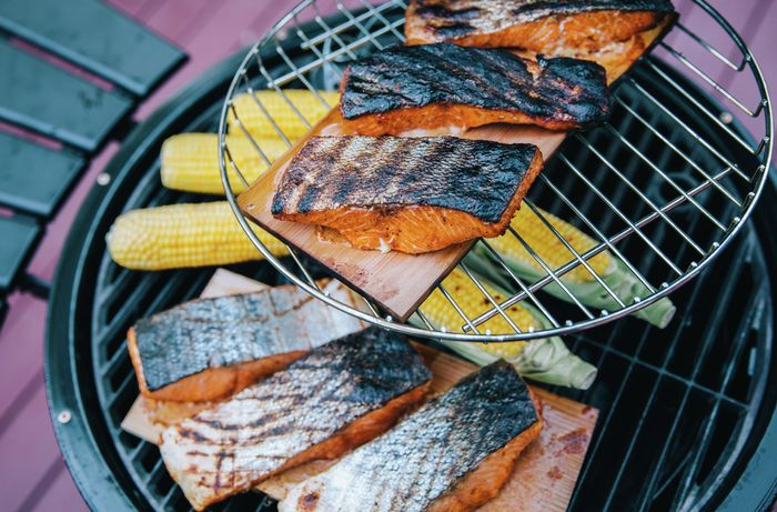 Fillets of salmon with charred skin on a serving board with corn cobs on a BBQ