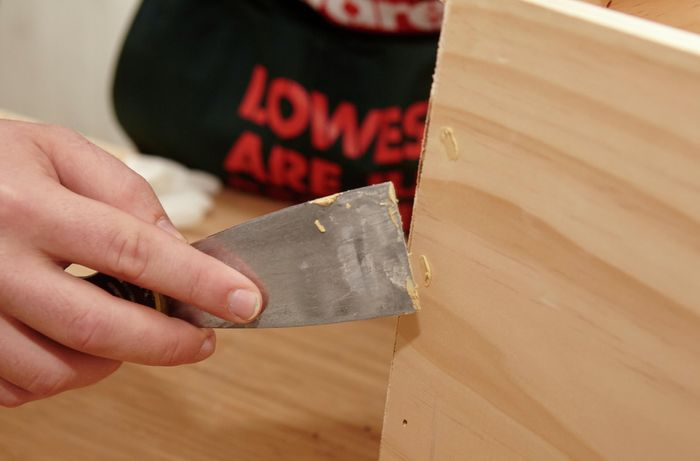 Person filling holes with timber filler and scraper.