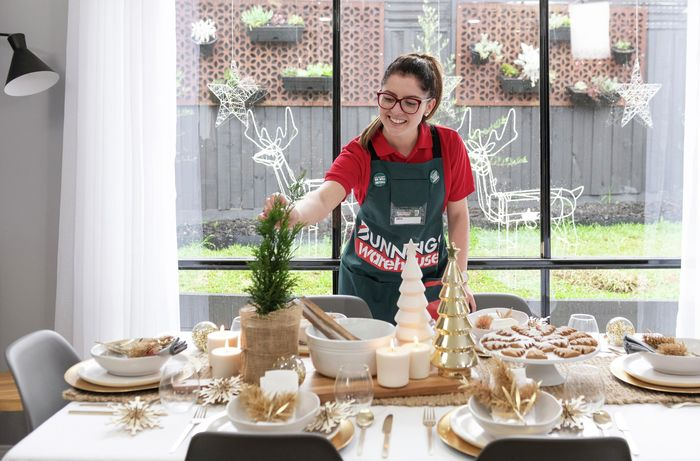 Woman adding finishing touches to dining table decorated for Christmas