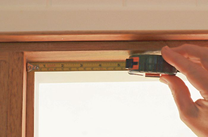 A tape measure being used to measure the length of a window, to allow for economic use of window seal